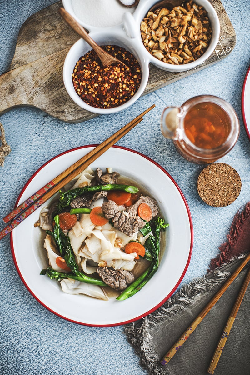This easy Rad Na recipe, a Thai stir-fry recipe, is a delicious noodle dish that is ladled with tasty, thick, gravy-like broth. #radnarecipe #thaistirfrywithgravy #noodlesingravy #widericenoodleswithgravy