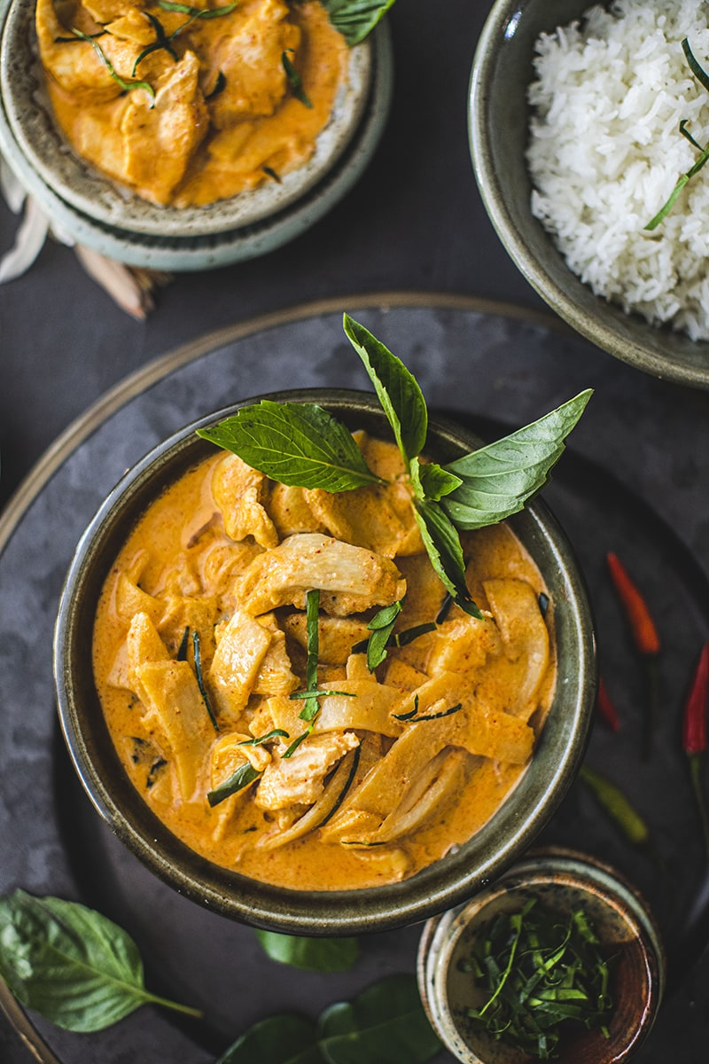bowl of chicken thai red curry with basil garnish with rice and smaller bowl in background.