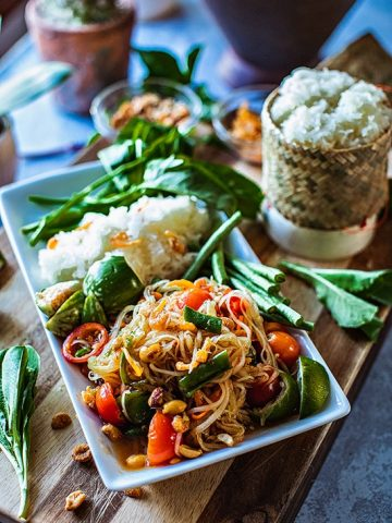 """Thai Papaya Salad or """"Som Tum"""" is an extremely flavorful salad made from green, unripe papaya lightly pounded together with garlic, Thai chilies, tomatoes, and green beans. The sweet, tangy, and sour taste comes from fresh lime juice, fish sauce, and palm sugar.#thaipapayasalad #papayasalad #thaisalad #greenpapayasalad"""