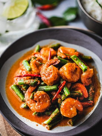 This easy red curry green beans with shrimp, or Pad Prik King, is a simple and delicious Thai dish that lightly fries red curry paste together with coconut cream, shrimp, kaffir lime leaves, and green beans.#redcurry #shrimpcurry #thaifood #thairedcurrry
