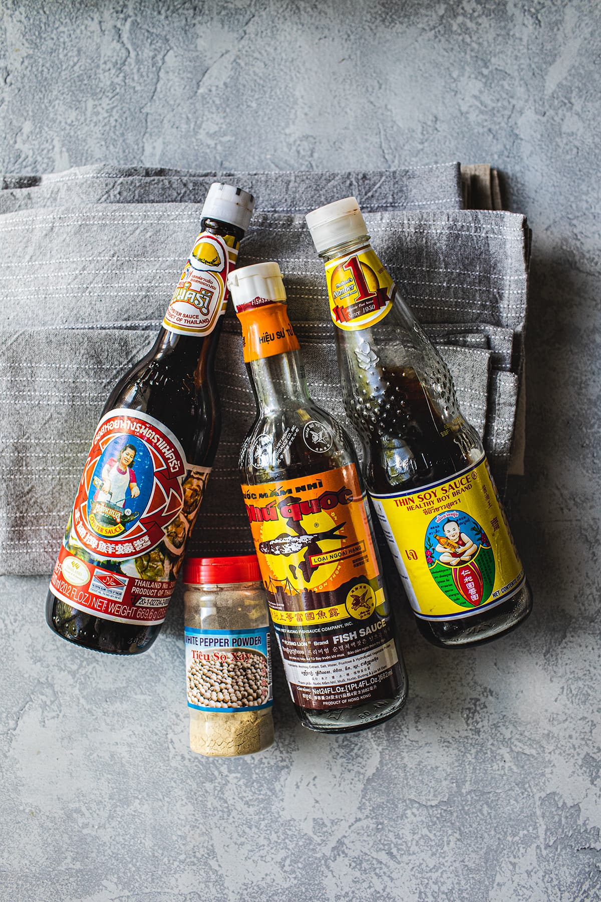 bottles of fish sauce, soy sauce, oyster sauce and ground white pepper