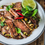 thai beef salad with sliced beef on a plate